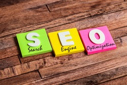Colorful square papers with wooden white letters for the English acronym word SEO means Search Engine Optimization