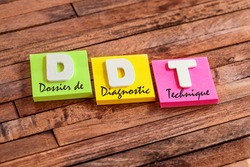 Colorful square papers with wooden white letters for the french acronym DDT means Technical Diagnostic Folder