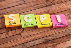 Colorful square papers with wooden white letters for the French acronym SCPI means Real estate Investment Company