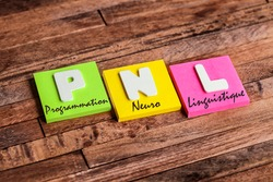 Colorful square papers with wooden white letters for the French acronym word PNL means NLP Neuro Linguistic Programming