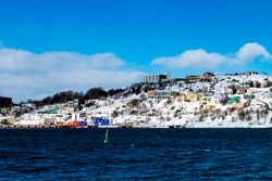 Colorful St. John's, Newfoundland, at winter with white snow on the ground. The buildings are bright colors and the sky is bright blue with some clouds. The houses are built on a steep hill.