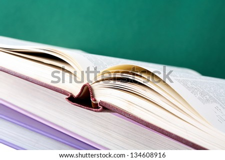 Colorful stack of textbooks with open book on its top
