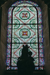 Colorful stained glass in a French Catholic church with a silhouette of statue of virgin in backlight