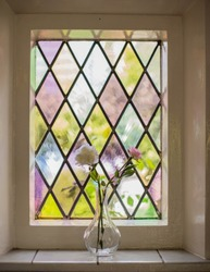 Colorful stained glass with flowers in  a vase in the light