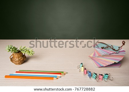colorful stationery. on the desktop beautifully folded colored stickers for notes, bright office binders and multi-colored pencils. in the vase a flower succulent #767728882