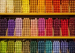 Colorful stick candles arranged in shelves and sorted by color in a candle shop.