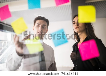 Colorful stickers on glass panel help female designer and her associate in job #741616411