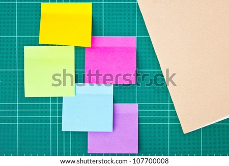 Colorful sticky notes and notebook on cutting mat.