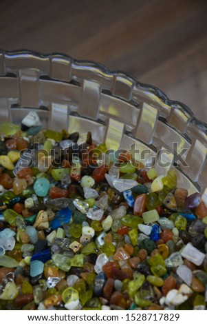 Colorful stone beads in glass bowl. Glass beads bright background. Craft project backdrop. Beading and hobby supplies #1528717829