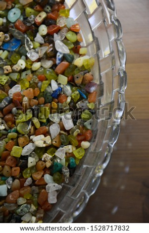 Colorful stone beads in glass bowl. Glass beads bright background. Craft project backdrop. Beading and hobby supplies #1528717832