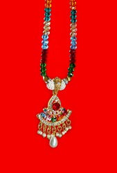 Colorful stones neckless imitation jewelry on red background