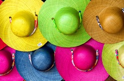 Colorful straw hats in a row