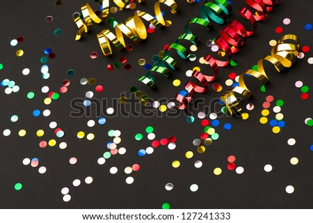 colorful streamer and confetti on black paper background. party decoration