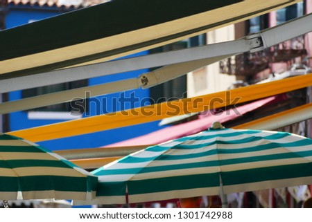Colorful striped parasols and awnings at a market, Burano, Italy, 2017 #1301742988