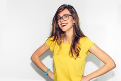 Colorful Studio Portrait of Hipster Fashion Smiling Girl with Hands on Hips at white Background. Fun positive young smart woman in glasses and colorful yellow shirt smiling with perfect teeth.