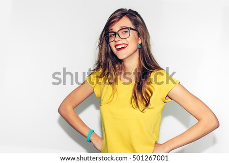 Colorful Studio Portrait of Hipster Fashion Smiling Girl with Hands on Hips at white Background. Fun positive young smart woman in glasses and colorful yellow shirt smiling with perfect teeth. #501267001