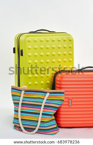 Colorful suitcases for summer your. Vertical image of bag on wheels, textile handbag. #683978236
