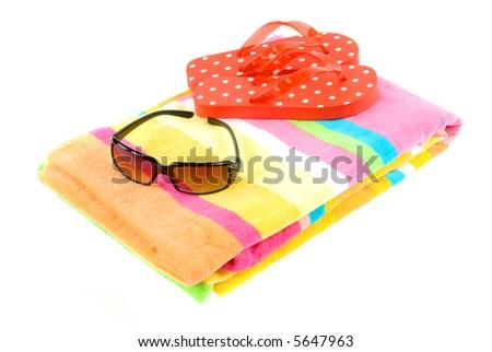 Colorful summer beachwear (flip flops), towel, and sunglasses
