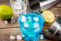 Colorful summer beverage, iced blue lagoon alcohol cocktail drink with lime and mint, bark background copy space