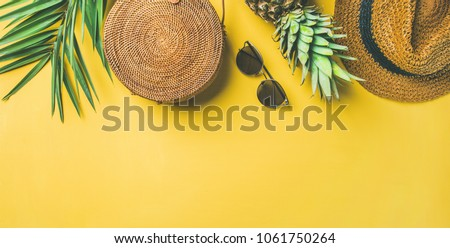 Colorful summer female fashion outfit flat-lay. Straw hat, bamboo bag, sunglasses, palm branches, pineapple over yellow background, top view, copy space, wide composition. Summer fashion, holiday #1061750264