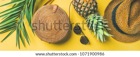 Colorful summer female fashion outfit flat-lay. Straw hat, bamboo bag, sunglasses, palm branches, pineapple over yellow background, top view, wide composition. Summer fashion, holiday concept #1071900986