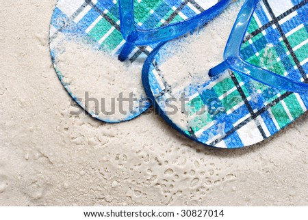 Colorful summer flip flops on wet sandy beach.  Macro showing texture and details.