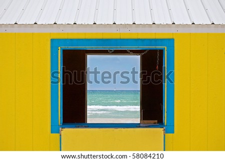 Colorful summer image of the ocean waters and blue sky framed by lifeguard house window. Architectural details