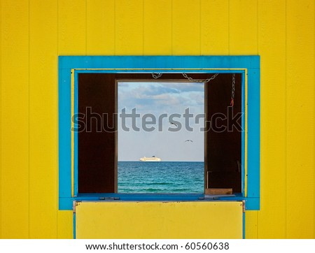 Colorful summer image of the ocean waters and blue sky framed by yellow lifeguard house window. Architectural details