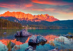 Colorful summer scene on the Eibsee lake in German Alps. Germany's highest mountain Zugspitze 2 962 m, and it's mountain ridge painted in red of the last rays of sunset. Germany, Europe.
