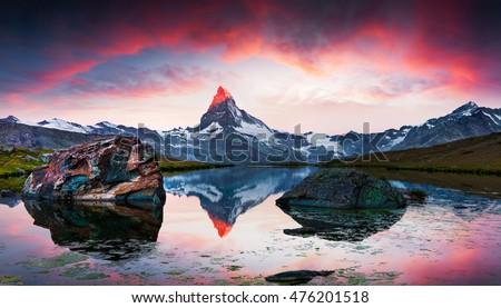 Colorful summer sunrise on the Stellisee lake. Reflection of Matterhorn peak in the watter surface. Beautiful outdoor scene in  Swiss Alps, Zermatt location, Valais canton, Switzerland, Europe.
