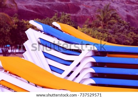 Colorful sunbeds stacked on Tenerife beach, Canary Islands. Retro filtered color tone. #737529571