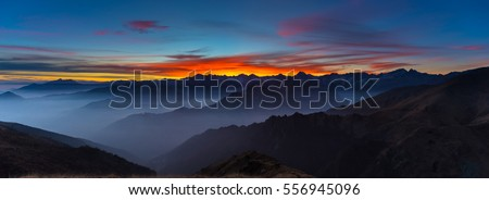Colorful sunlight behind majestic mountain peaks of the Italian - French Alps, viewed from distant. Fog and mist covering the valleys below, autumnal landscape, cold feeling. #556945096