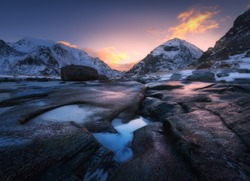 Colorful sunrise in Utakleiv beach, Lofoten islands, Norway. Amazing scene with snowy mountains, stones, beautiful reflection in water, red sky, clouds. Winter landscape. Coast with stones in water