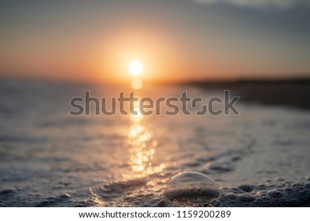 Colorful sunrise with details of waves and bubbles with blurry background bokeh. Danish beach , Lønstrup in North Jutland in Denmark, Skagerrak, North Sea