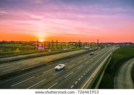 Colorful sunset at M1 motorway near Flitwick junction with blurry cars in United Kingdom
