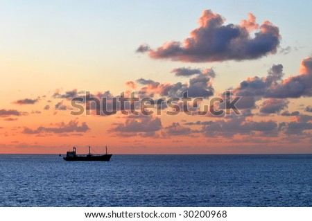 Colorful sunset at sea with merchant ships