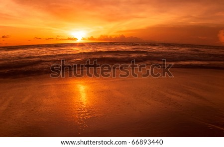 Colorful sunset at the sand tropical beach. Legian beach on Bali island. Indonesia