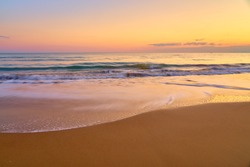 Colorful sunset at the tropical beach, sun behind clouds reflects on water and waves with foam hitting sand.