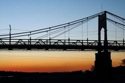 Colorful sunset behing the pillar of a steel bridge