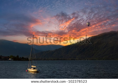 Colorful sunset on Lake, with yacht on water and air baloon in the sky, Alps mountains on background