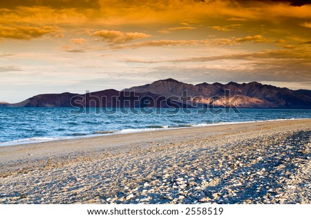 Colorful sunset on the sandy beach with mountainous islands in the background.