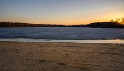 Colorful sunset on the shore of a lake in early spring. The sun is hiding behind the trees in the background. The surface half covered with ice.