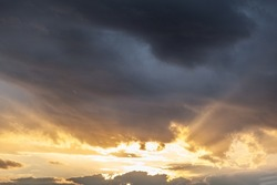Colorful sunset or sunrise in the sky. The sun's rays are visible through the clouds. The sky and clouds are painted in different delicate colors. Beautiful background.