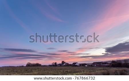 Colorful sunset over a field foreground #767866732