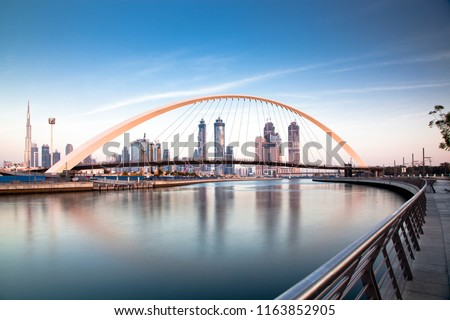 colorful sunset over Dubai Downtown skyscrapers and the newly built Tolerance bridge as viewed from the Dubai water canal. #1163852905