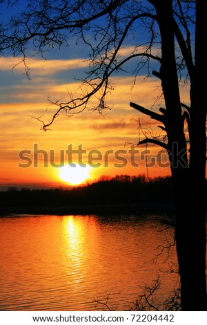Colorful sunset over the river in early spring