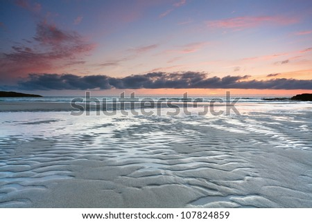 Colorful sunset over tidal beach of Tangasdale, Isle of Barra, Outer Hebrides, Scotland.