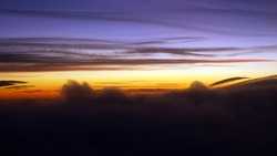 Colorful sunset seen from an airplane window. Cloud silhouette photo taken kilometers high.