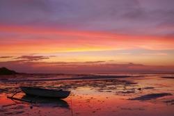 Colorful sunset with outrigger fishing boat on Walakiri beach near Waingapu on Sumba island, East Nusa Tenggara, Indonesia