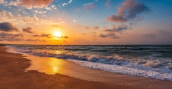 Colorful sunset with wave splashes on the beach